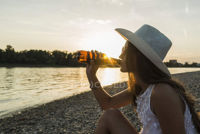 Young woman drinking beer at the riverside at sunset — Stock Photo