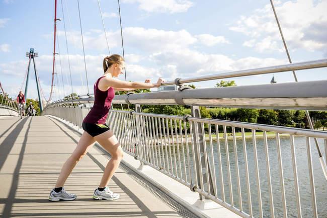 Молодой спортсмен, растянувшийся на мосту — стоковое фото