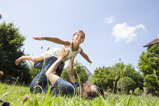 Caucasian father playing with daughter in garden — Stock Photo