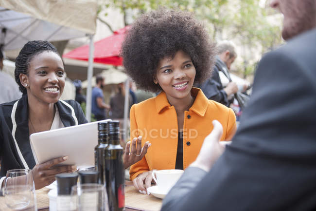 Colleagues talking while sitting at outdoor restaurant — Stock Photo