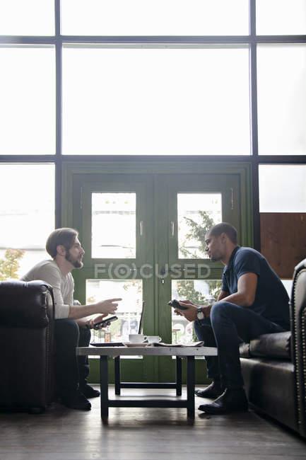 Due uomini con i dispositivi portatili che si siede sul divano in un salotto — Foto stock