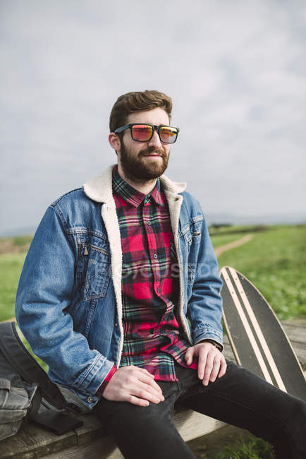 Young casual man with sunglasses sitting on bench — Stock Photo