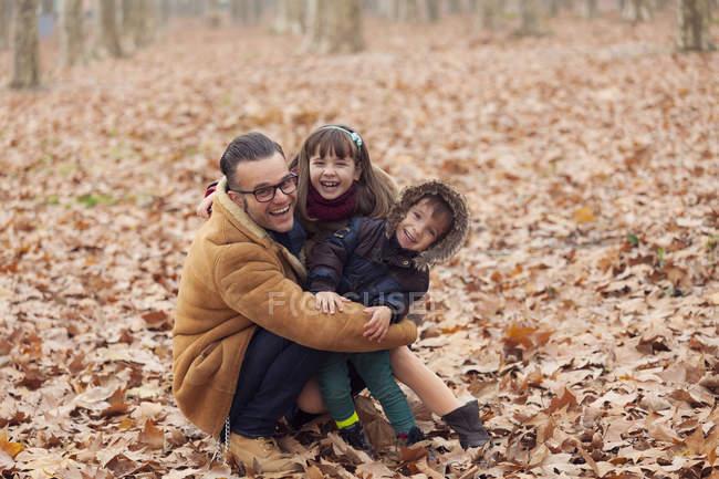 Padre con figli felici nel parco autunnale seduto in foglie — Foto stock