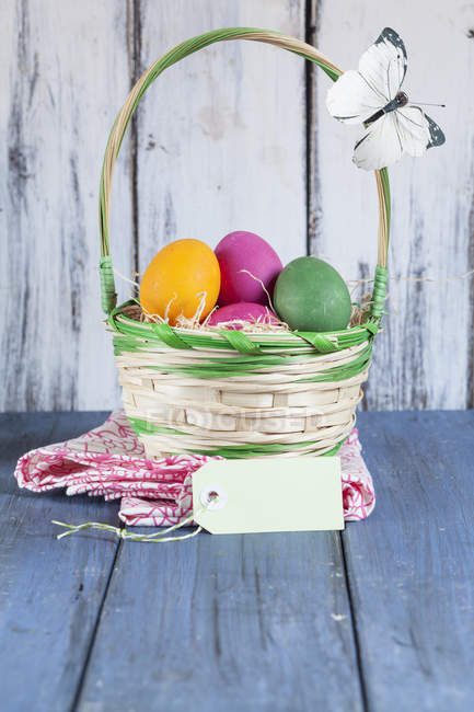 Colorful Easter basket with tag and butterfly decoration — Stock Photo