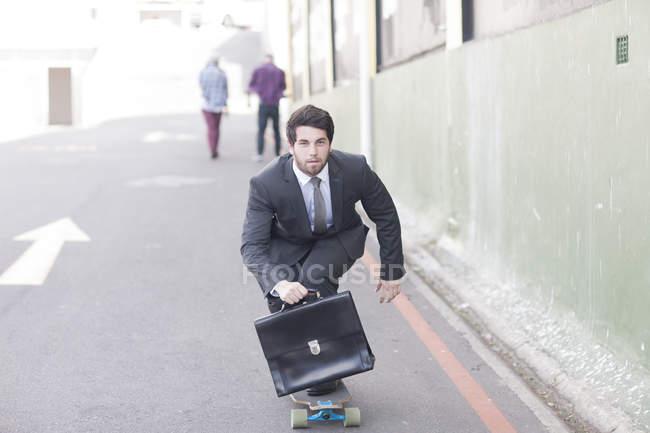 Businessman on skateboard riding down the street — Stock Photo