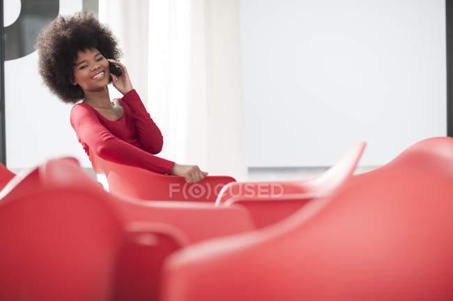 Jeune femme au bureau assise sur une chaise rouge parlant sur un téléphone portable — Photo de stock