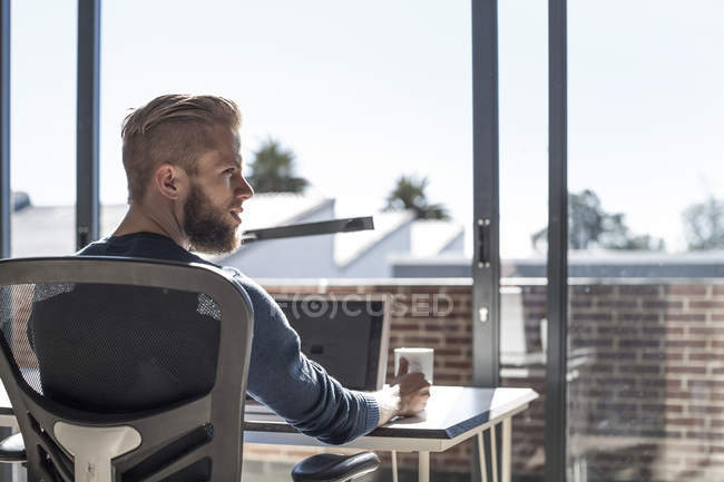 Giovane seduto alla scrivania, che lavora in ufficio — Foto stock
