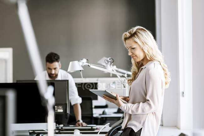 Two colleagues in office with digital tablet and computer — Stock Photo