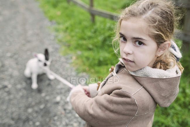 Portrait of little girl walking with French bulldog on background — Stock Photo