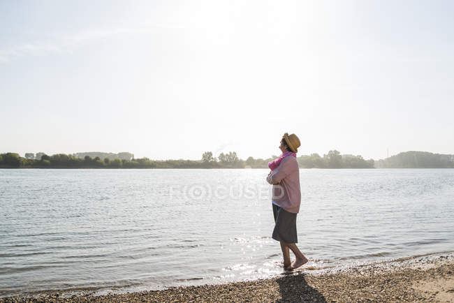 Senior woman relaxing at riverside — Stock Photo