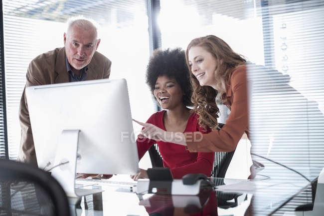 Three colleagues in office looking at computer screen — Stock Photo