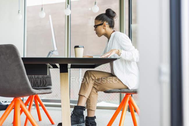 Giovane donna in ufficio che lavora al computer — Foto stock