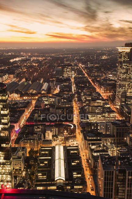 Germania, Francoforte, vista elevata sulla città con stazione centrale illuminata al crepuscolo di sera — Foto stock