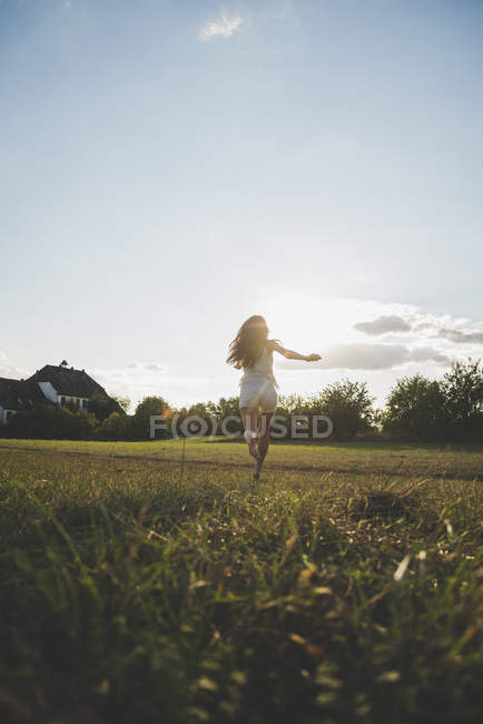 Back view of woman running barefoot on a meadow at backlight — Stock Photo