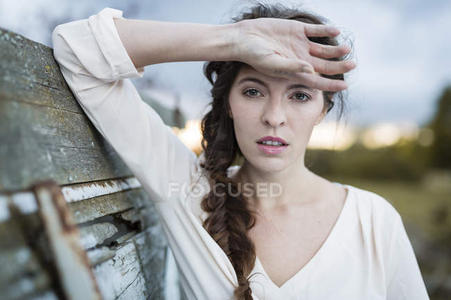 Portrait of woman with hand on forehead at twilight — Stock Photo