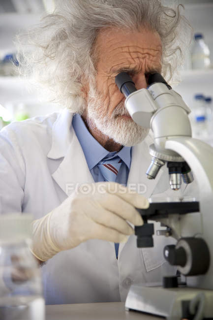 Tousled professor examining samples under microscope — Stock Photo