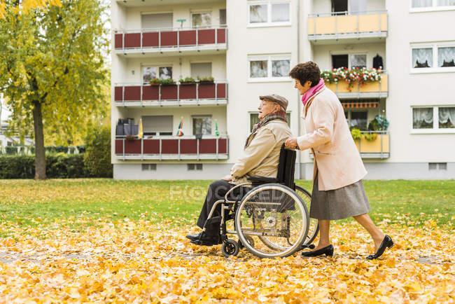 Старший женщина, толкая мужа в инвалидной коляске — стоковое фото