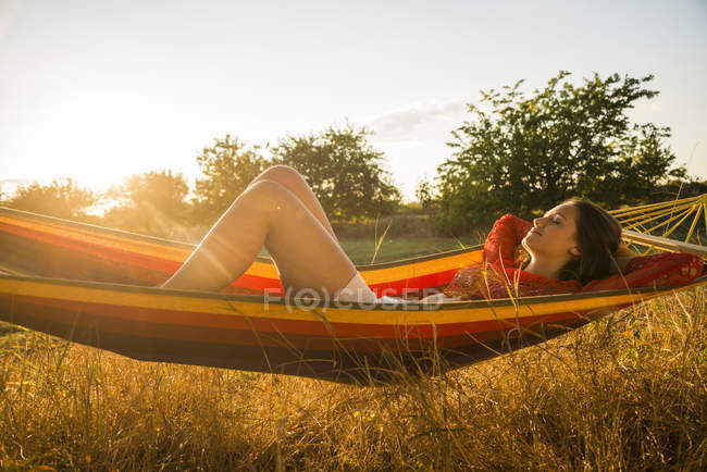Woman relaxing in a hammock at backlight — Stock Photo
