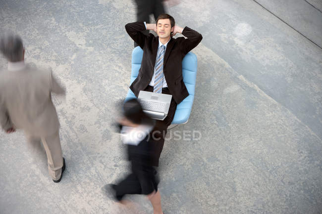 Businessman with laptop having a break with people passing by — Stock Photo