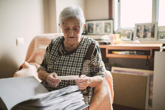 Senior woman watching old photos of her childhood — Stock Photo