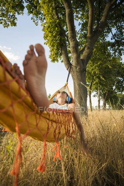 Женщина с наушниками, лежа в гамаке, отдыха на природе — стоковое фото