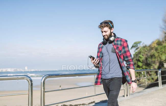 Hipster con cuffie utilizzando smartphone sul lungomare — Foto stock