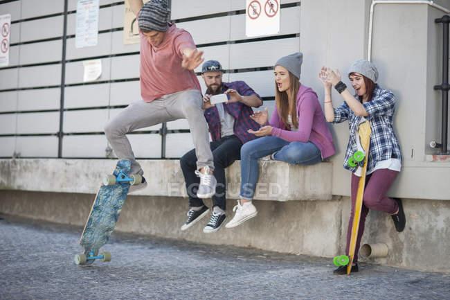 Jeune homme avec des amis, faire un truc de skateboard — Photo de stock