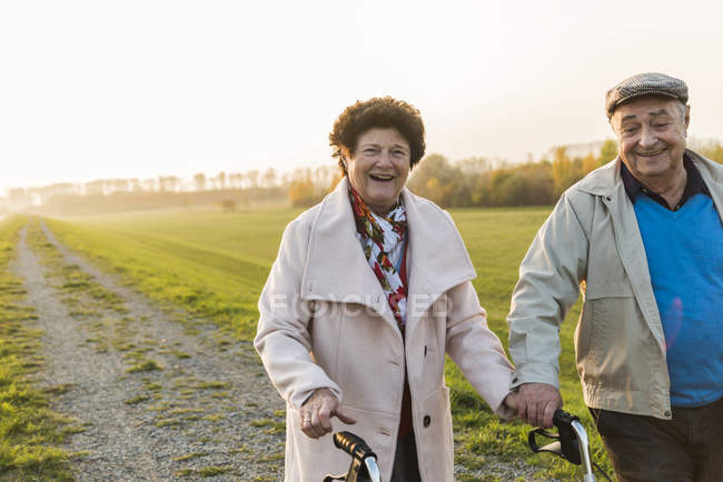 Smiling senior couple with wheeled walker in the nature — Stock Photo