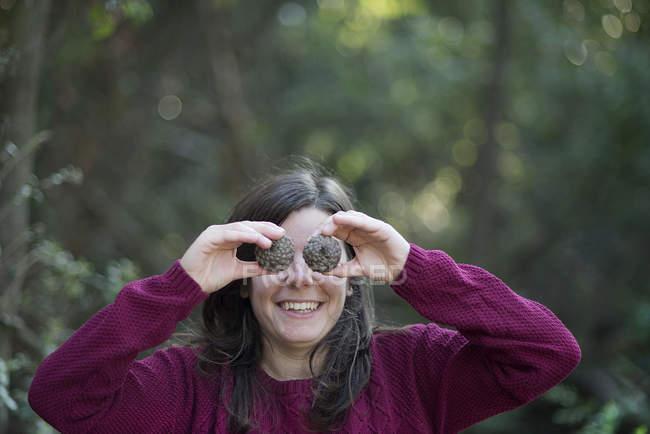 Портрет улыбающейся молодой женщины, закрывающей глаза сосновыми шишками — стоковое фото