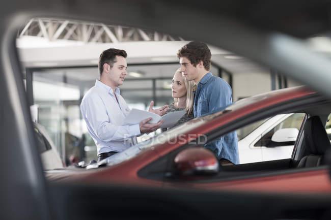 Продавец автомобилей показывает брошюру молодой паре в выставочном зале — стоковое фото