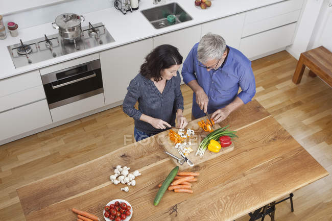 Casal maturo preparar legumes na cozinha — Fotografia de Stock