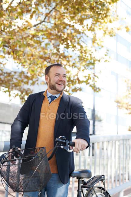 Retrato de homem de negócios feliz com bicicleta na cidade — Fotografia de Stock