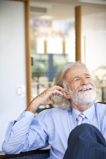 Laughing senior man sitting in chair, portrait — Stock Photo
