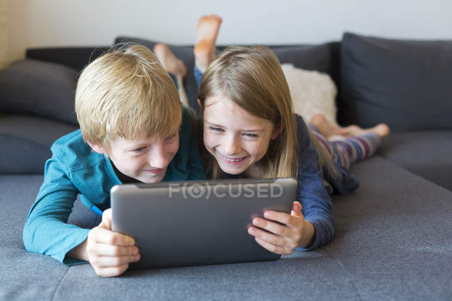 Boy and girl lying side by side on the couch using digital tablet — Stock Photo