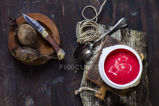 Vista superior da sopa de beterraba em tigela no tabuleiro — Fotografia de Stock