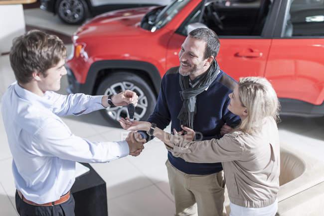 Торговец автомобилями дает ключ клиенту — стоковое фото