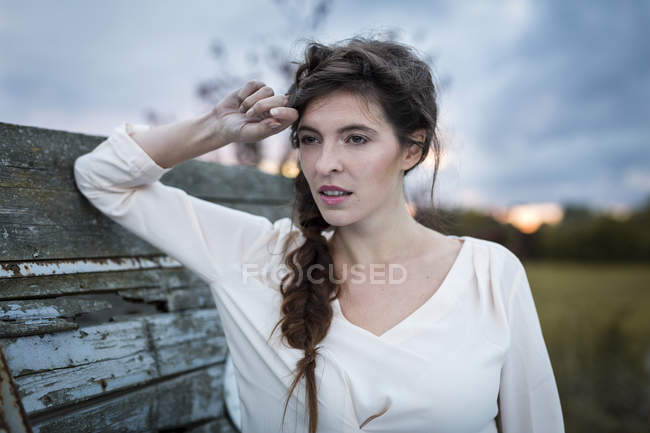 Woman with braid looking at distance on rural background — Stock Photo