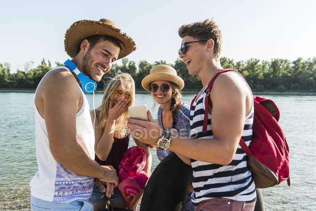 Glückliche Freunde teilen Handy am Fluss — Stockfoto