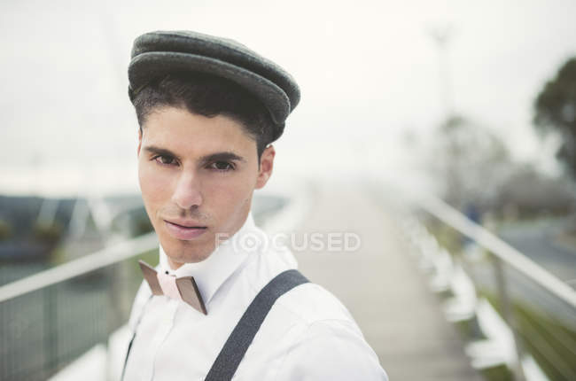 Portrait of young man wearing beret and a wooden bow tie — Stock Photo