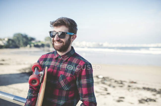 Smiling hipster wearing sunglasses with skateboard on beach — Stock Photo