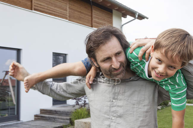 Pai adulto carregando filho feliz no jardim — Fotografia de Stock