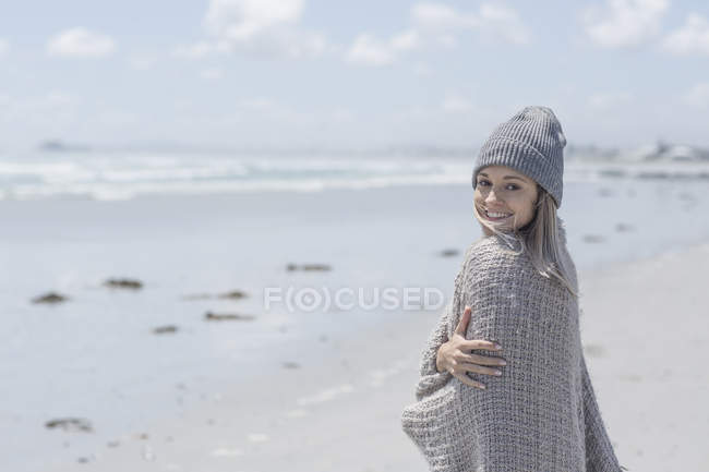 Portrait of smiling woman wearing beanie and wrap on the beach — Stock Photo