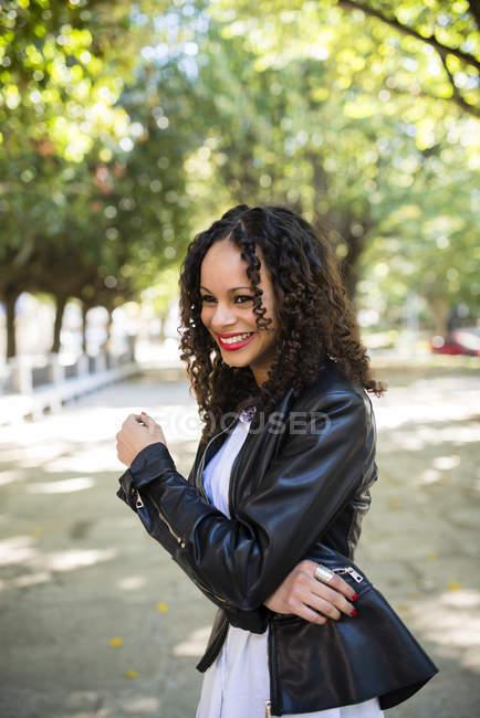 Улыбающаяся женщина стоит в парке — стоковое фото