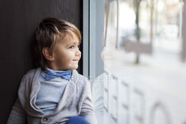 Portrait de petit garçon souriant avec nœud papillon regardant à travers l'affichage de la fenêtre — Photo de stock