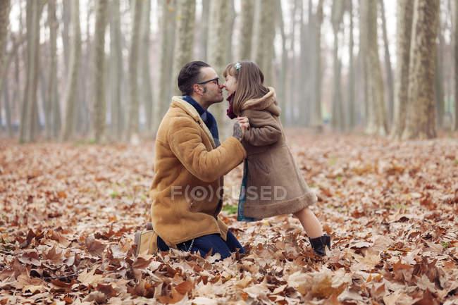 Отец целует свою дочь в осеннем парке, сидя в листьях — стоковое фото