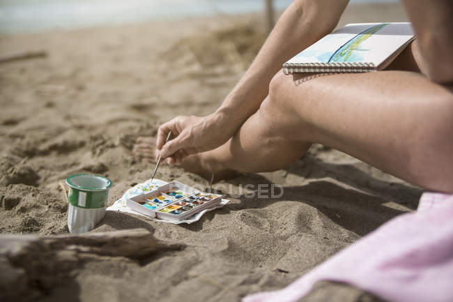 Cropped image of Woman painting on beach — Stock Photo
