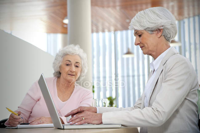 Two senior women working together at laptop — Stock Photo