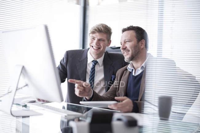 Dois colegas na mesa olhando para a tela do computador — Fotografia de Stock
