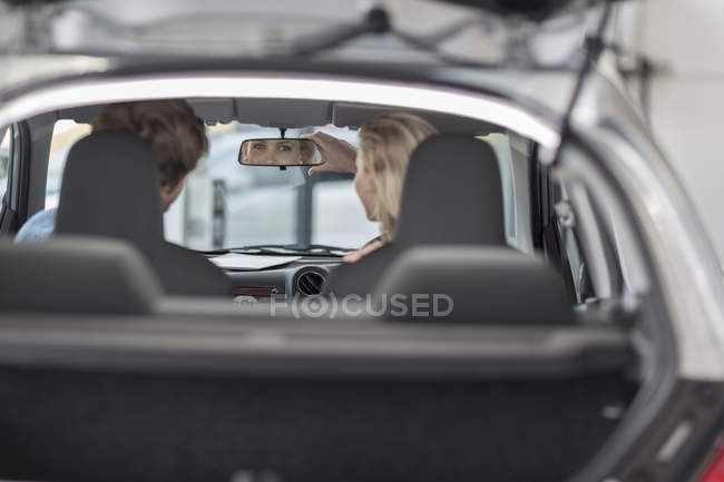 Young couple sitting in new car at car dealership — Stock Photo