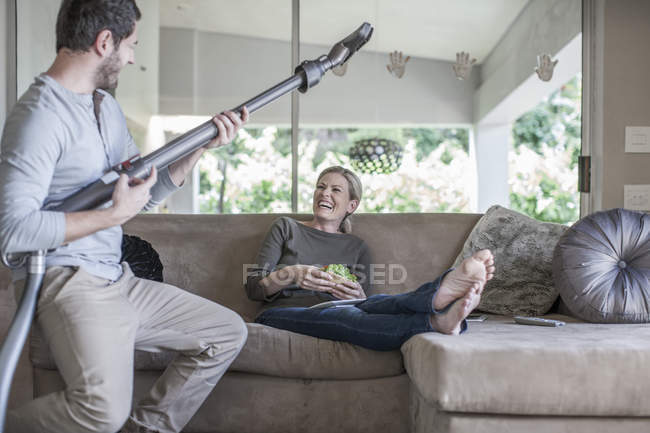 Woman On Couch And Man Pretending Playing Guitar With Vacuum Cleaner U2014  Color Image, Two People   Stock Photo | #178102324